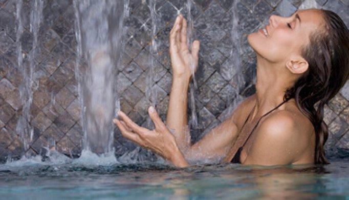 Frau unter Wasserfall
